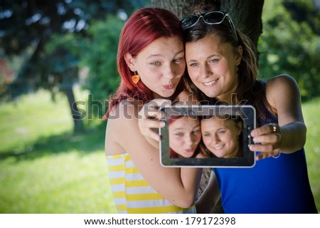 Two pretty young women teenage girlfriends students sitting in park with tablet pc taking selfshot or selfy picture of themselves on summer green outdoors background, - stock photo