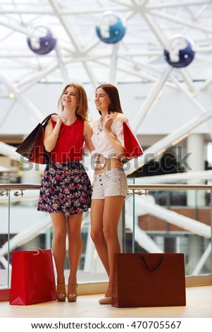 Two pretty young women with purchases stand and smile in modern mall