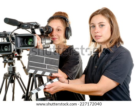 two pretty young women work with a video camera on the white background - stock photo