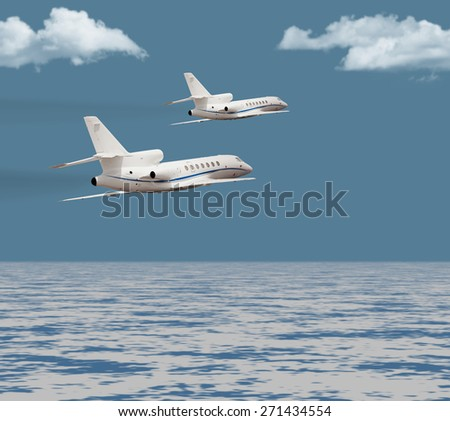 Two private jets flying over the ocean  - stock photo