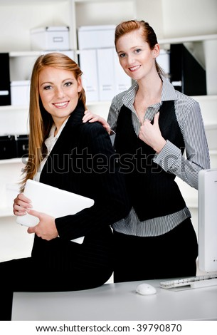 Two professional and attractive businesswomen with a laptop and a computer in the office