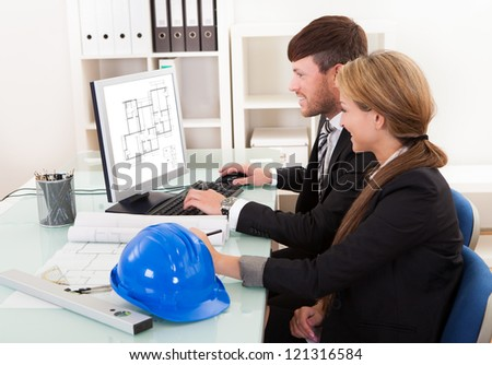 Two professional architects or structural engineers sitting at a desk looking at a computer discussing a building plan - stock photo