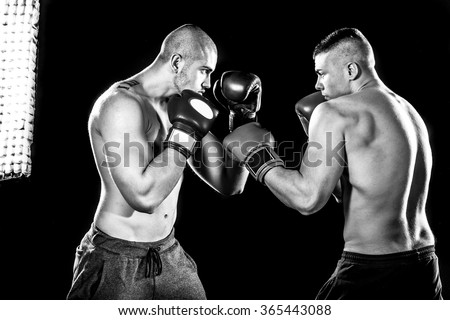 Two professional boxer isolated on black background, black and white photography, in studio low key with flash light  - stock photo