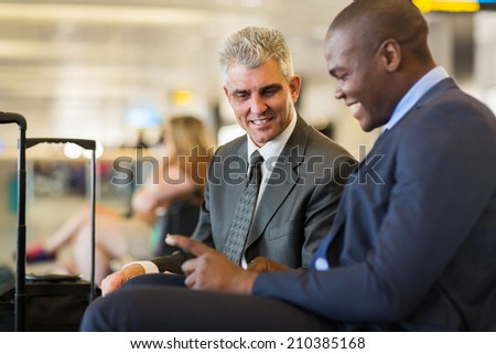 two professional business partners at airport waiting for their flight - stock photo