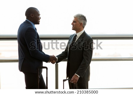 two professional businessmen hand shaking at airport - stock photo