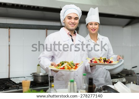 Two professional cooks working at restaurant kitchen  - stock photo