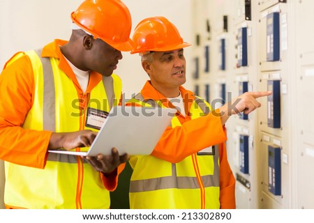 two professional electricians checking industrial control box - stock photo