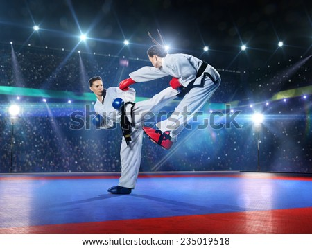 Two professional female karate fighters are fighting on the grand arena - stock photo