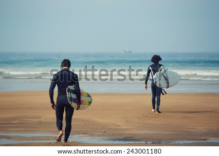 Two professional surfers carrying their surfboards while going to the sea, professional surfers in black diving suits ready to surf walk to the ocean - stock photo