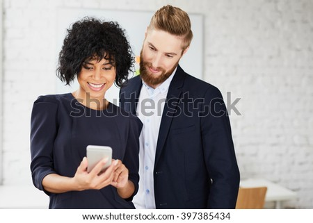 Two professionals, business people looking at smartphone in the office - stock photo