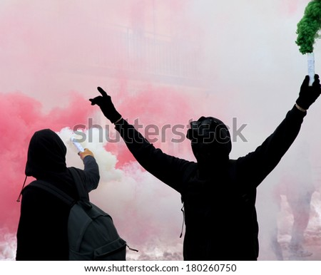 two protesters after a soccer match with the smoke on the street