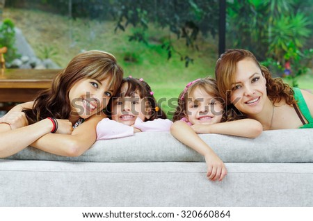 Two proud hispanic mothers posing with their daughters, heads sticking up from sofa and smiling to camera. - stock photo