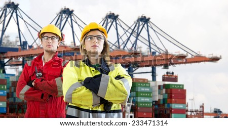 Two proud looking dockers, wearing safety attire with their arms crossed standing in front of a huge container ship being unloaded in an industrial harbour.  - stock photo