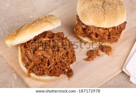 Two pulled pork barbecue sandwiches on a cutting board - stock photo