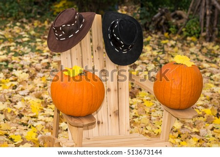 Two pumpkins and hats on a wooden chair