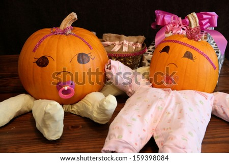 Two pumpkins dressed up as princess babies with pacifiers on a table beside gifts. - stock photo