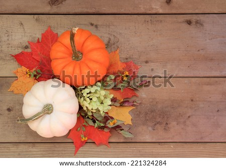 Two pumpkins on wood background with autumn leaves and flowers. Halloween or Thanksgiving decor.