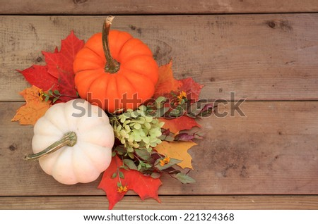 Two pumpkins on wood background with autumn leaves and flowers. Halloween or Thanksgiving decor. - stock photo