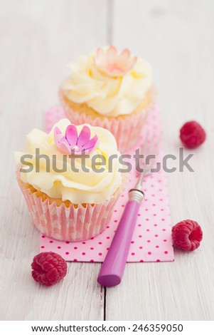 Two purple cupcakes with buttercream frosting swirl, raspberries and edible flowers - stock photo