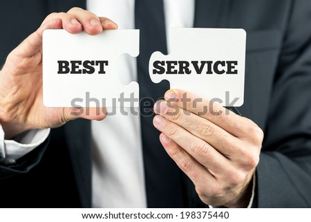 Two puzzle pieces with the phrase - Best service - spread across them and a businessman moving the second piece into position to complete the puzzle. - stock photo