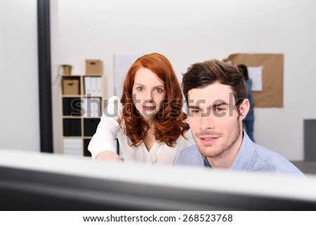 Two puzzled business colleagues looking at a desktop monitor together with frowning expressions - stock photo