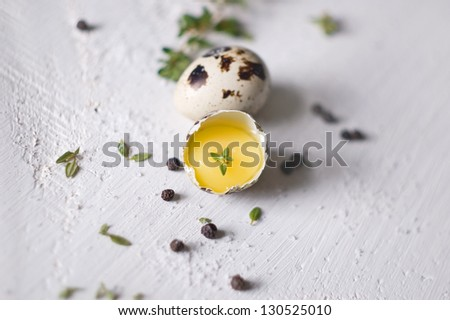 Two quail eggs on white wooden table - stock photo