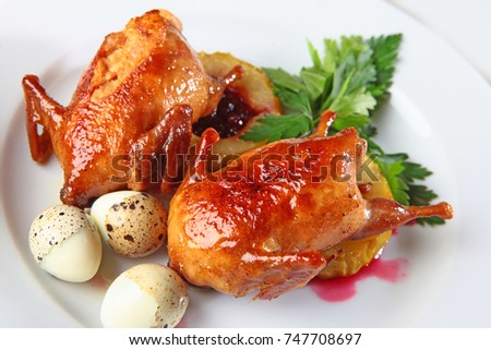 Two quails on a plate with quail eggs. Game. Macro photo. White background.
