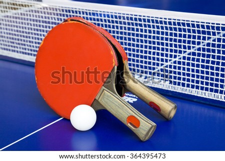 Two rackets for ping-pong on a blue table.