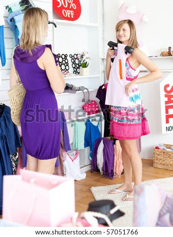 Two radiant women choosing clothes together in a shop