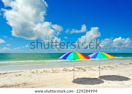 Two Rainbow Colored Beach Umbrellas on the Beach - stock photo