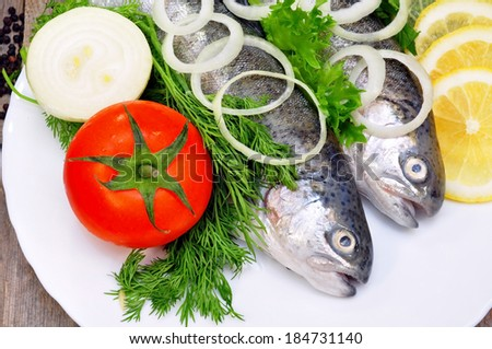 two rainbow trout with lemon and fresh vegetables  - stock photo