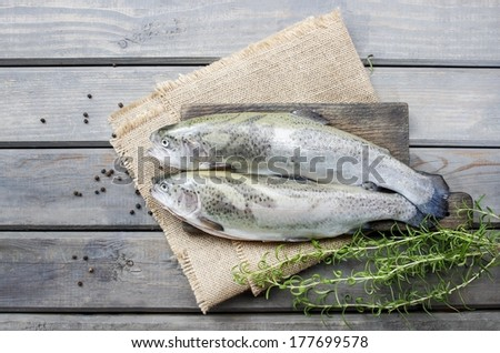 Two rainbow trouts on rustic wooden table - stock photo
