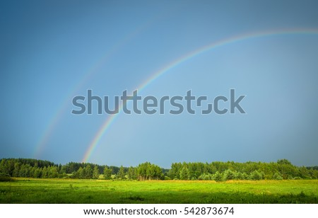 two rainbows over the green field