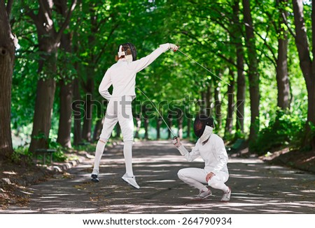 Two rapier fencer women fighting over park alley, attacking each other in jumping - stock photo