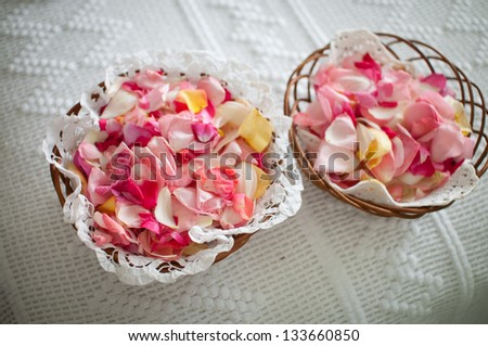 two rattan baskets full of rose petals to throw at the wedding shallow depth of field photo - stock photo