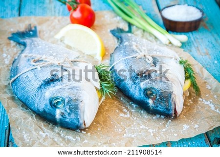 two raw dorada fishes with lemon, green onions and cherry tomatoes on a rustic background