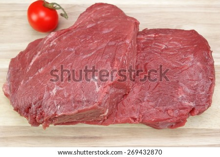Two Raw Farm Fresh Beef Steaks For Barbecue And Ripe Tomato Close-Up On White Wood Cutting Board Background - stock photo