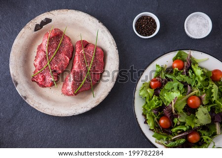Two raw fillet steaks with a green salad and cherry tomatoes on a slate background - stock photo