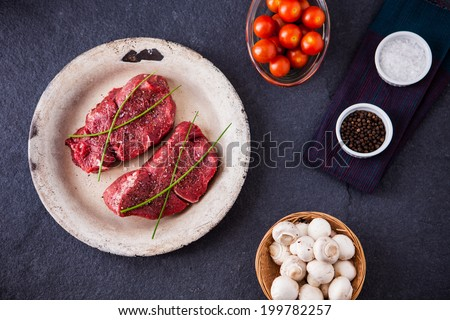 Two raw fillet steaks with mushrooms, cherry tomatoes, salt and pepper on a slate background