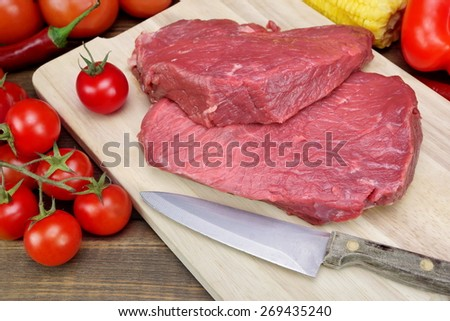 Two Raw Fresh Beef Steak And Tomato Close-Up On Wood Cutting Board Background - stock photo