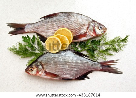 Two raw fresh fishes on marble table with lemon, dill and parsley. Crucian fishes. top view, flat lay. - stock photo