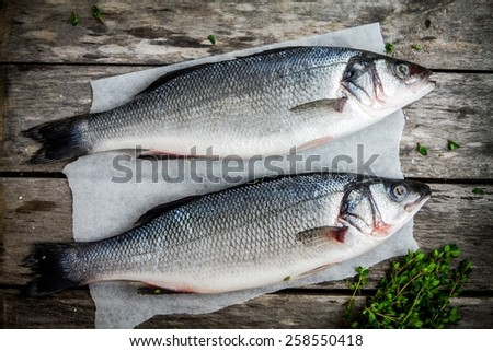 two raw sea bass with fresh thyme on wooden rustic table - stock photo