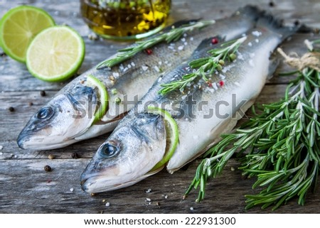 Two raw seabass with lime and rosemary on the wooden background - stock photo