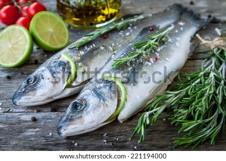 Two raw seabass with lime, cherry tomatoes and rosemary on the wooden background - stock photo