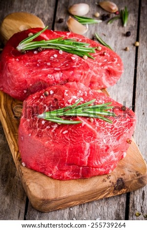 two raw steaks with rosemary, garlic, salt and pepper in olive cutting board - stock photo