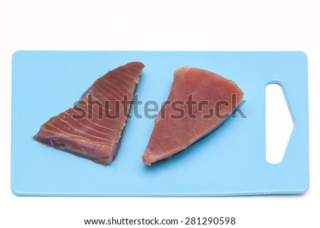 Two raw tuna steaks on blue cutting board. - stock photo