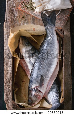Two Raw uncooked seebass fish in wood box with dry herbs over old wooden background. Top view - stock photo
