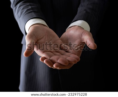 Two reaching out hands close-up shot of a caucasian man in a business suit, low-key dramatic light composition - stock photo
