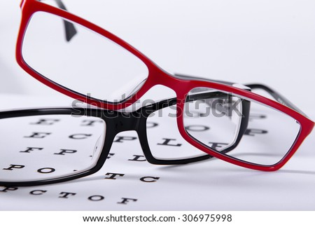 two reading red and black eyeglasses and eye chart close-up on a light background - stock photo