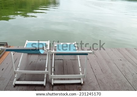 Two Recline chairs on dock facing a green lake. - stock photo